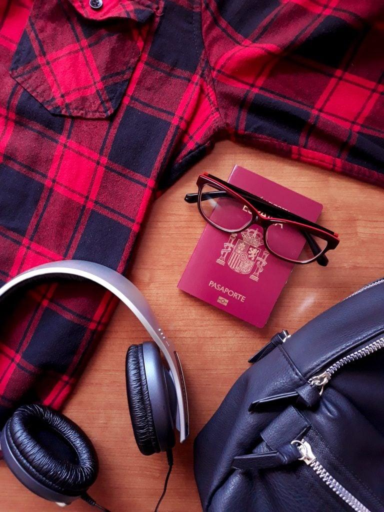 Pasaporte, gafas, camisa de cuadros y cascos.